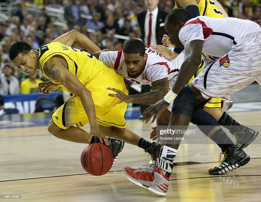 Trey Burke #3 of the Michigan Wolverines and Chane Behanan #21 of the Louisville Cardinals go after a loose ball in the second half during the 2013 NCAA Men's Final Four Championship at the Georgia Dome on April 8, 2013 in Atlanta, Georgia.