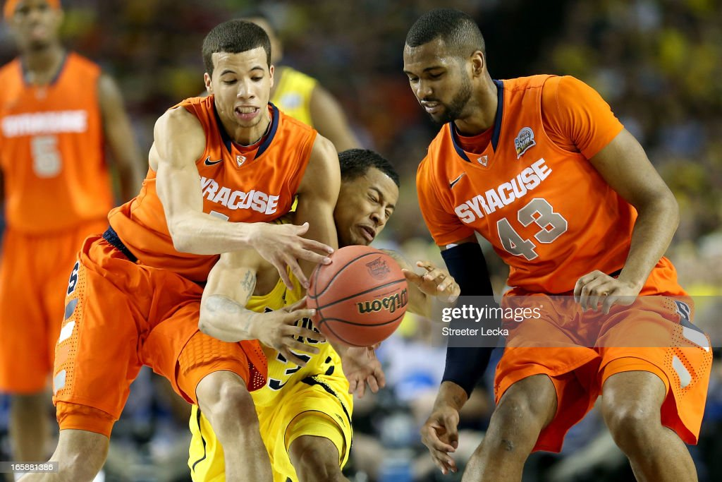 Trey Burke #3 of the Michigan Wolverines attempts to control the ball in the first half against Michael Carter-Williams #1 and James Southerland #43 of the Syracuse Orange during the 2013 NCAA Men's Final Four Semifinal at the Georgia Dome on April 6, 2013 in Atlanta, Georgia.