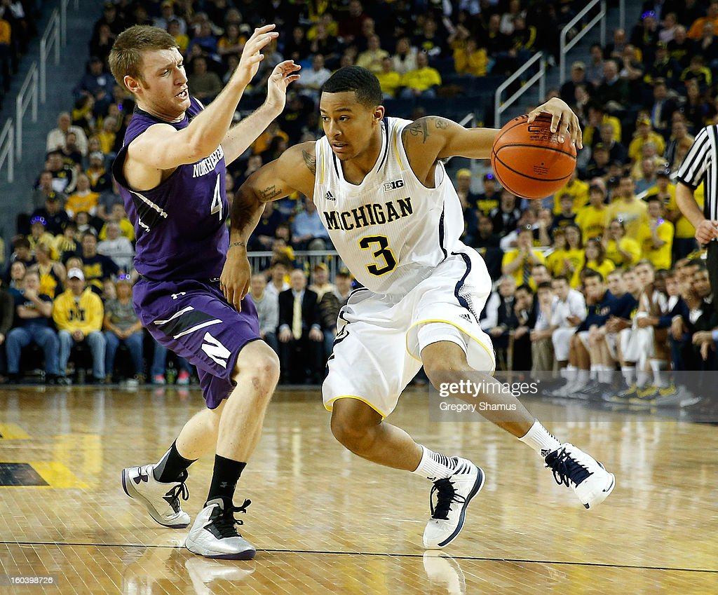 Trey Burke #3 of the Michigan Wolverines drives around Alex Marcotullio #4 of the Northwestern Wildcats during the first half at Crisler Center on January 30, 2013 in Ann Arbor, Michigan.
