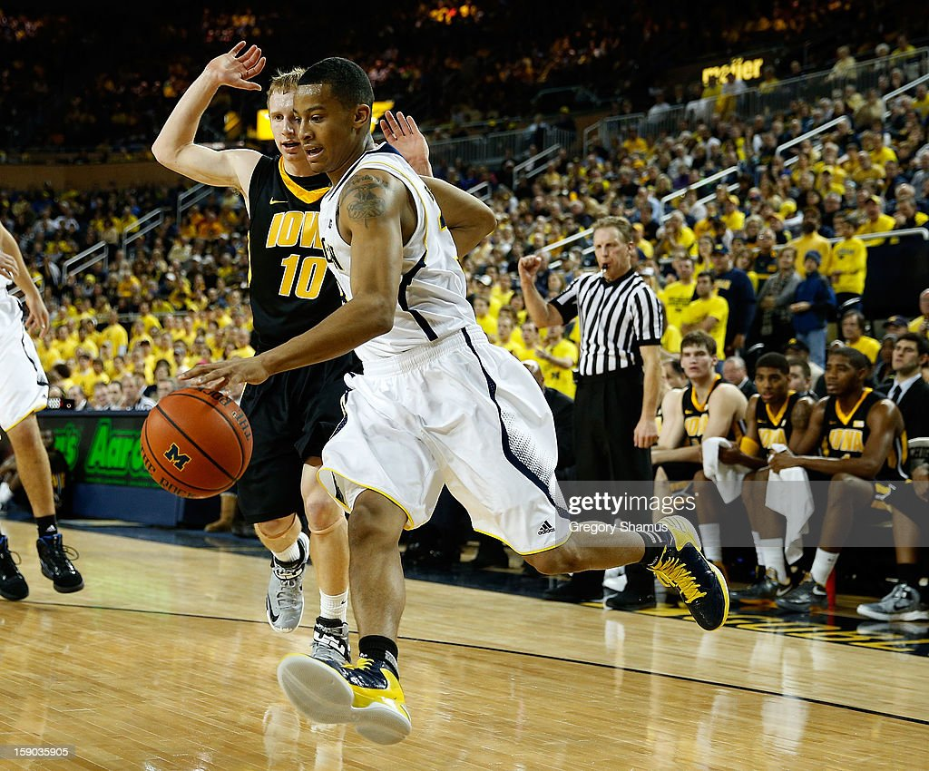 Trey Burke #3 of the Michigan Wolverines drives around Mike Gesell #10 of the Iowa Hawkeyes during the first half at Crisler Center on January 6, 2013 in Ann Arbor, Michigan.
