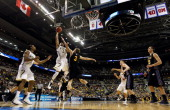 Trey Burke of the Michigan Wolverines drives for a shot attempt against Nate Wolters of the South Dakota State Jackrabbits during the second round of...