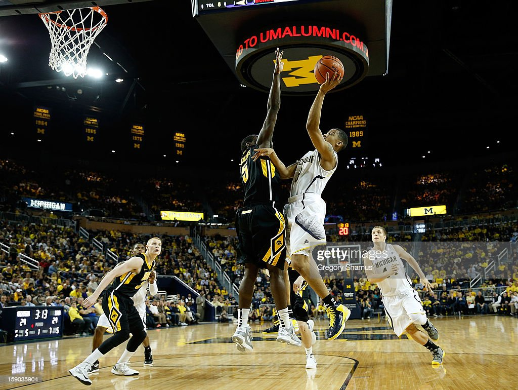Trey Burke #3 of the Michigan Wolverines gets a first half shot off over Anthony Clemmons #5 of the Iowa Hawkeyes at Crisler Center on January 6, 2013 in Ann Arbor, Michigan.