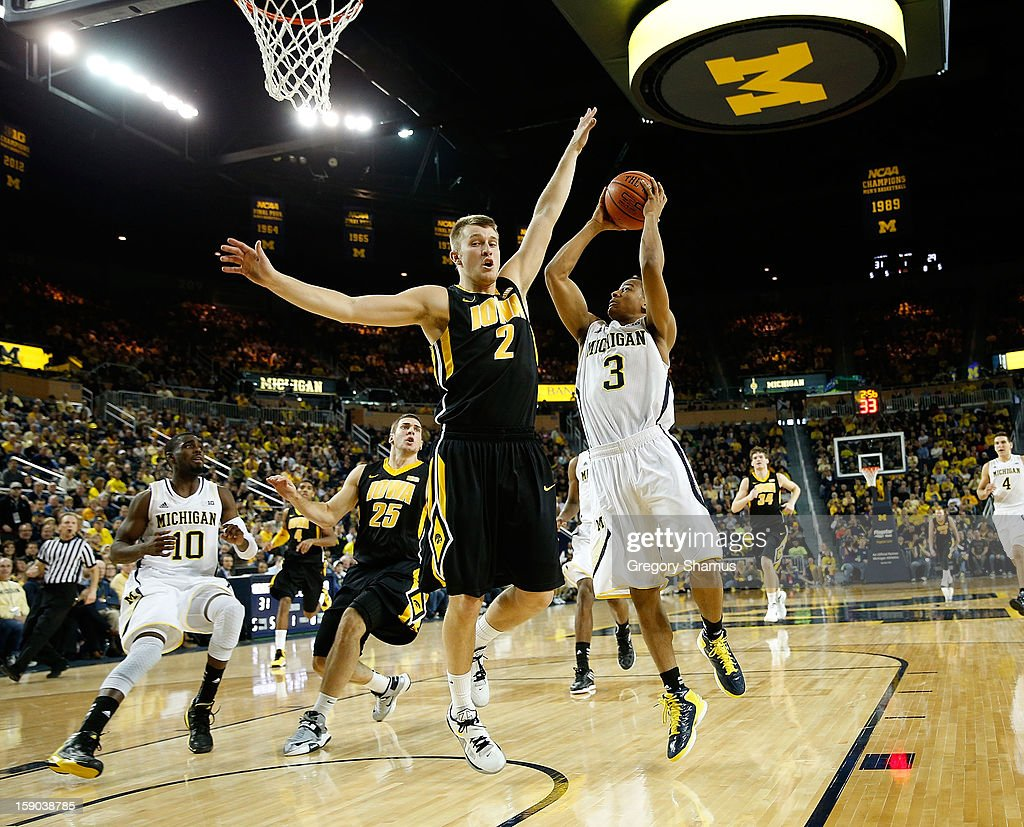 Trey Burke #3 of the Michigan Wolverines gets off a first half shot next to Josh Oglesby #2 of the Iowa Hawkeyes at Crisler Center on January 6, 2013 in Ann Arbor, Michigan. Michigan won the game 95-67.