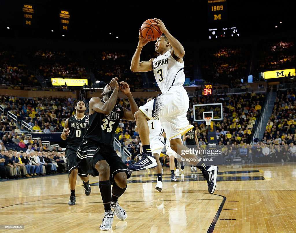 Trey Burke #3 of the Michigan Wolverines gets to the basket past Rapheal Davis #35 of the Purdue Boilermakers during the first half at Crisler Center on January 24, 2013 in Ann Arbor, Michigan. Michigan won the game 68-53.