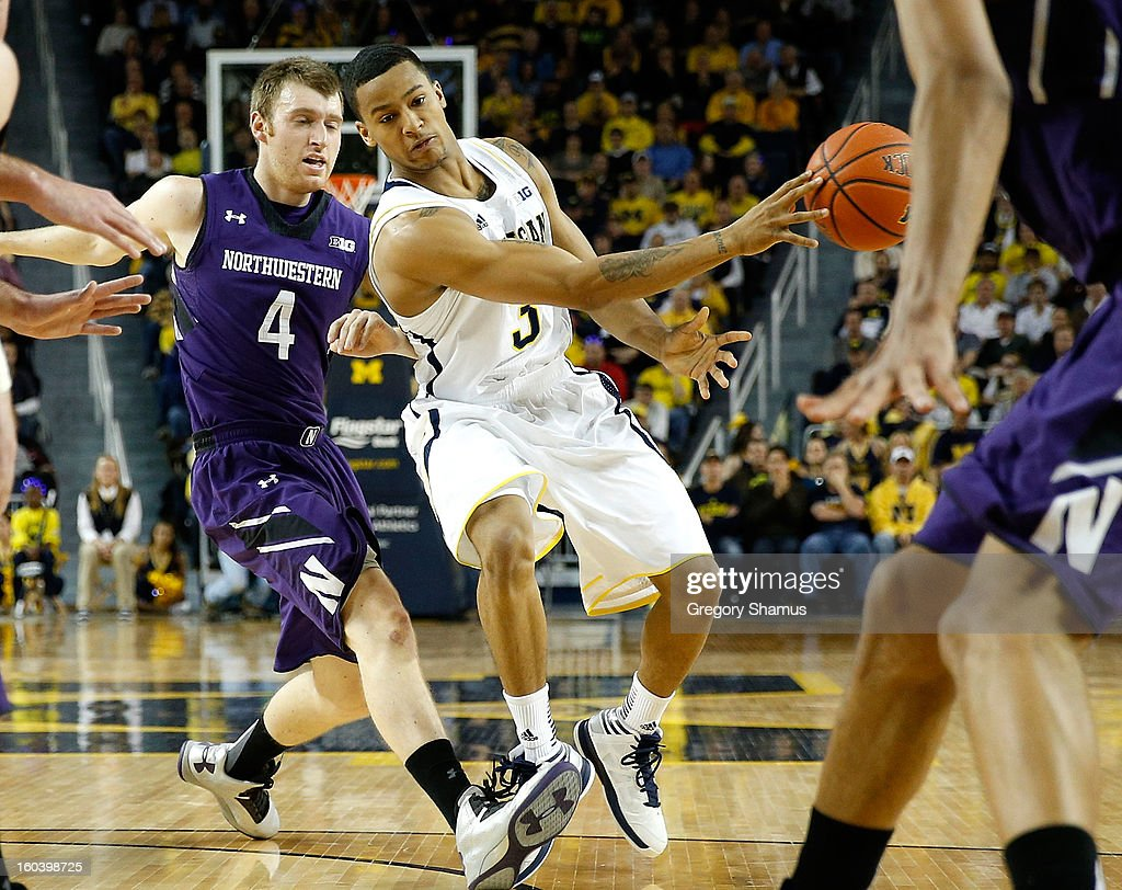 Trey Burke #3 of the Michigan Wolverines passes to a teammate in front of Alex Marcotullio #4 of the Northwestern Wildcats during the first half at Crisler Center on January 30, 2013 in Ann Arbor, Michigan.
