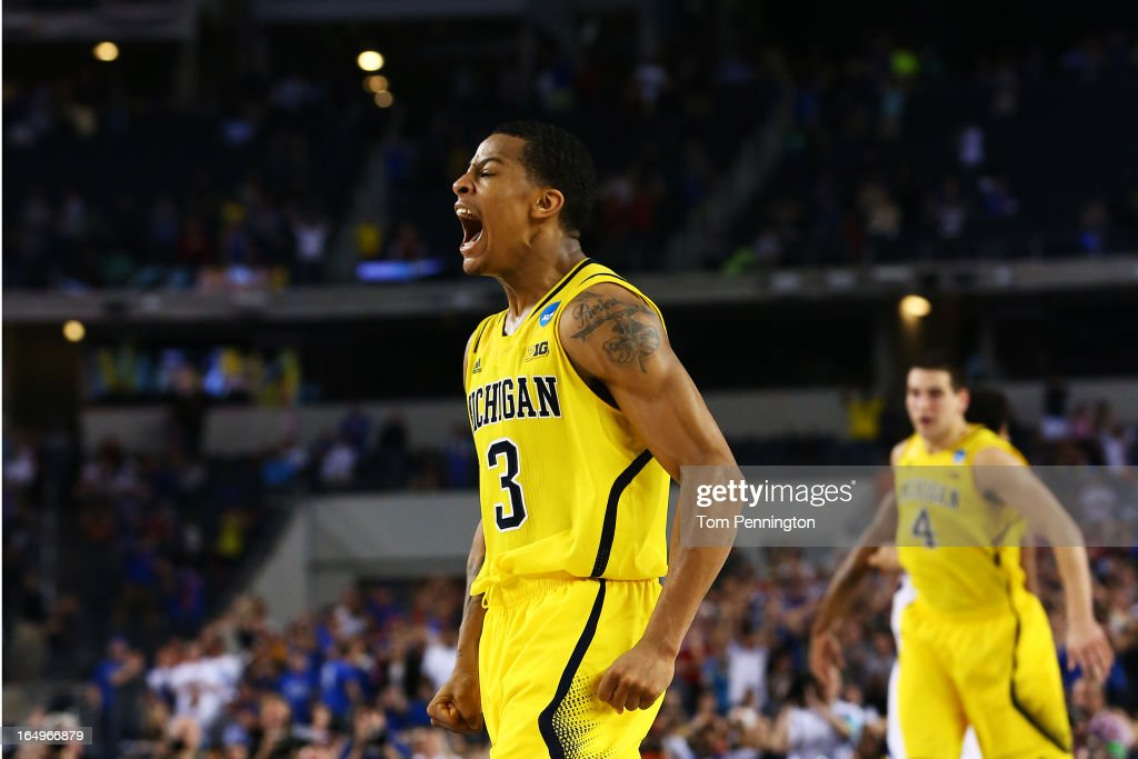 Trey Burke #3 of the Michigan Wolverines reacts after shooting a game tying three pointer in the final seconds of the second half againist the Kansas Jayhawks during the South Regional Semifinal round of the 2013 NCAA Men's Basketball Tournament at Dallas Cowboys Stadium on March 29, 2013 in Arlington, Texas.