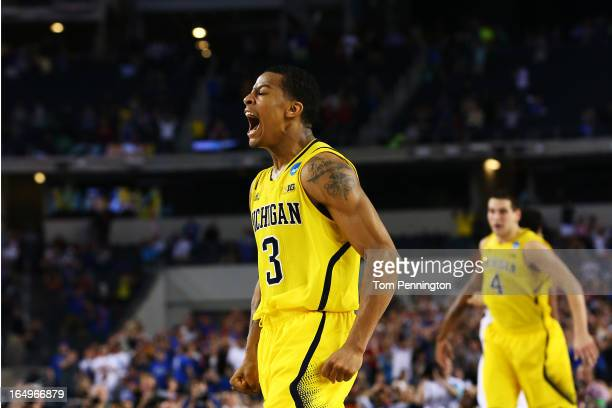 Trey Burke of the Michigan Wolverines reacts after shooting a game tying three pointer in the final seconds of the second half againist the Kansas...