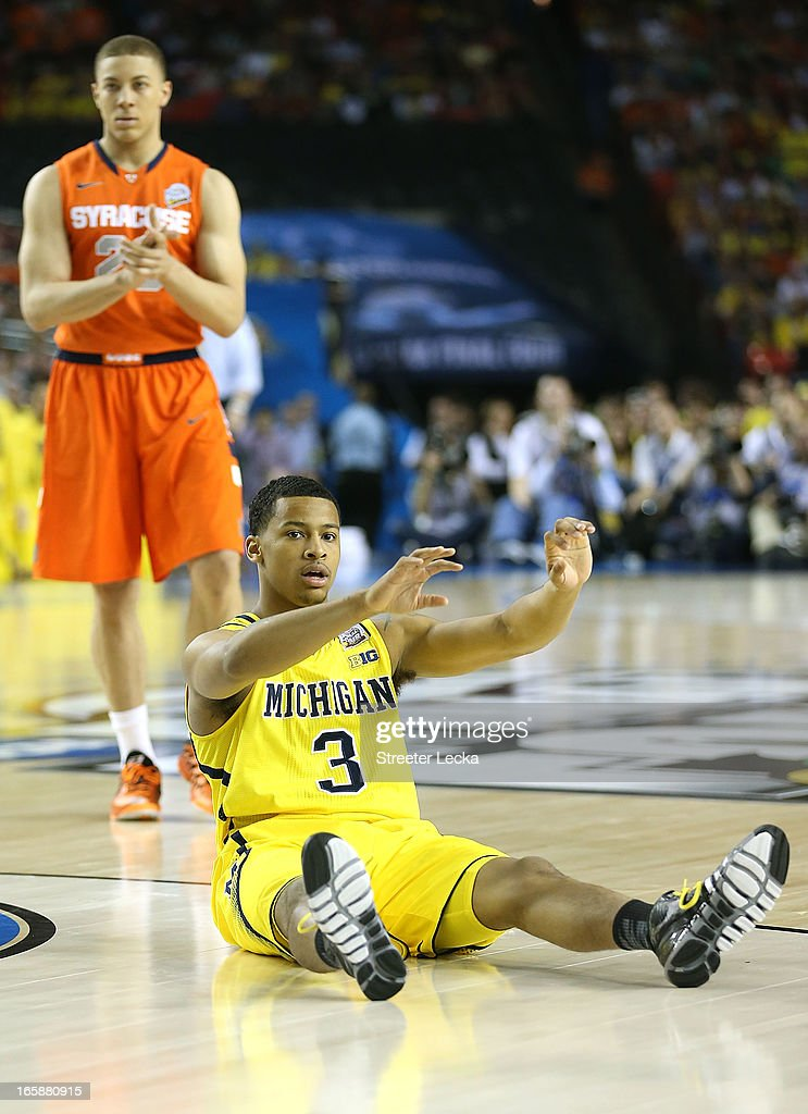 <a gi-track='captionPersonalityLinkClicked' href=/galleries/search?phrase=Trey+Burke&family=editorial&specificpeople=8770717 ng-click='$event.stopPropagation()'>Trey Burke</a> #3 of the Michigan Wolverines reacts in the first half against <a gi-track='captionPersonalityLinkClicked' href=/galleries/search?phrase=Brandon+Triche&family=editorial&specificpeople=6516120 ng-click='$event.stopPropagation()'>Brandon Triche</a> #20 of the Syracuse Orange during the 2013 NCAA Men's Final Four Semifinal at the Georgia Dome on April 6, 2013 in Atlanta, Georgia.