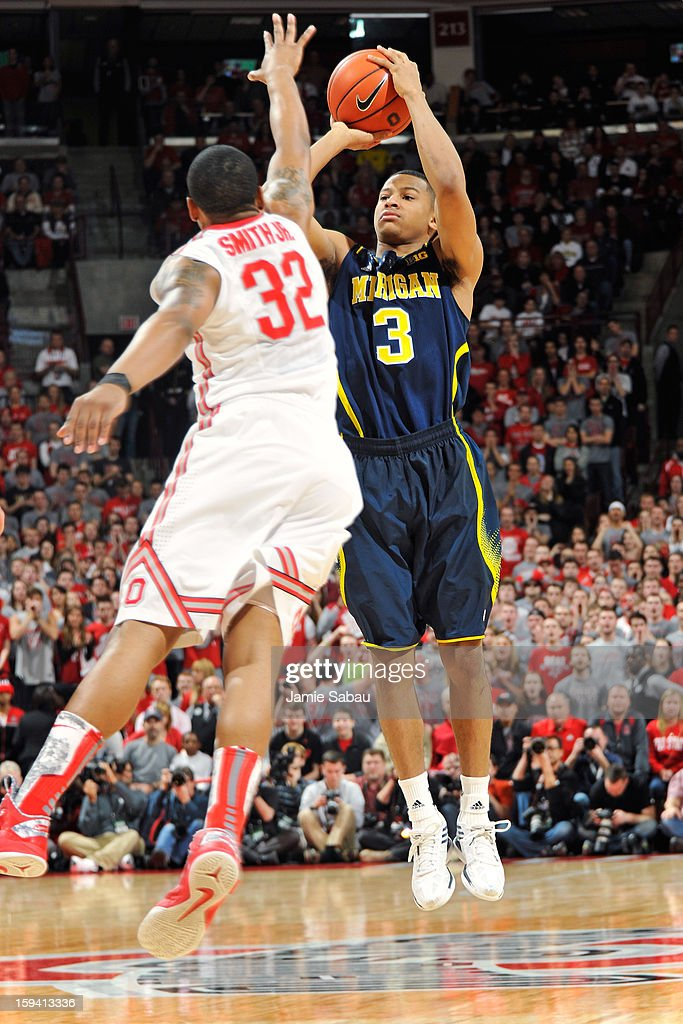 Trey Burke #3 of the Michigan Wolverines shoots a three-point shot for the first points of the game over Lenzelle Smith, Jr. #32 of the Ohio State Buckeyes in the first half on January 13, 2013 at Value City Arena in Columbus, Ohio.