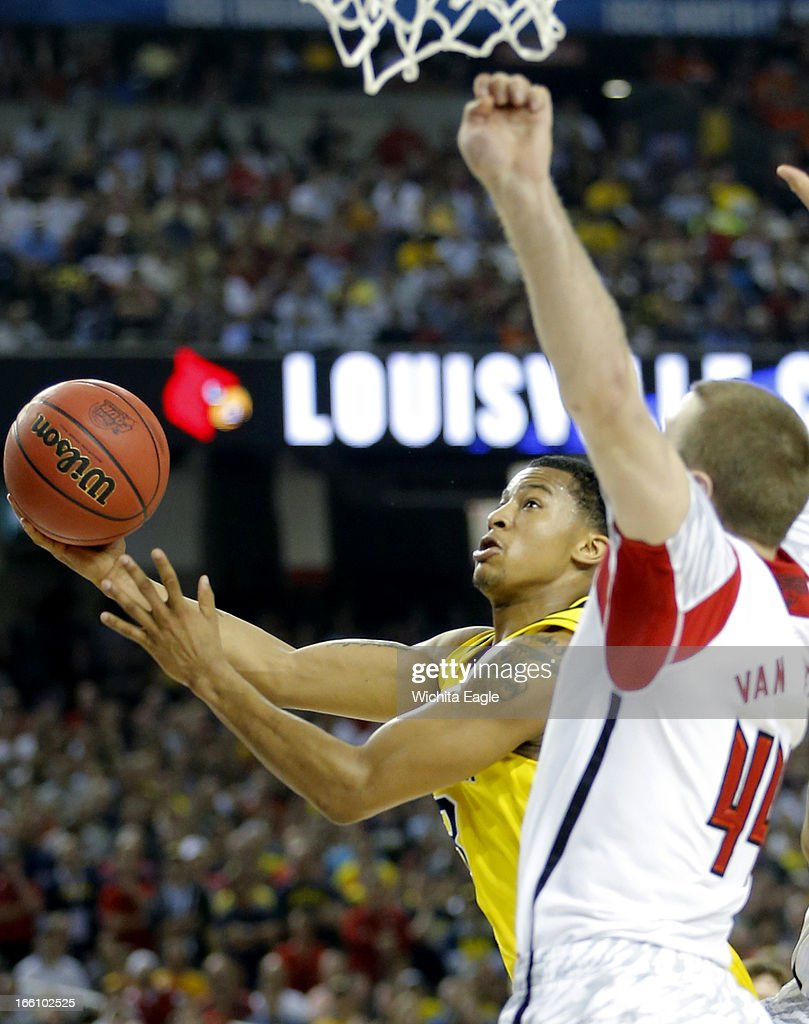 Trey Burke (3) of the Michigan Wolverines shoots against Stephan Van Treese (44) of the Louisville Cardinals in the NCAA Men's Basketball Championship at the Georgia Dome in Atlanta, Georiga, Monday, April 8, 2013.