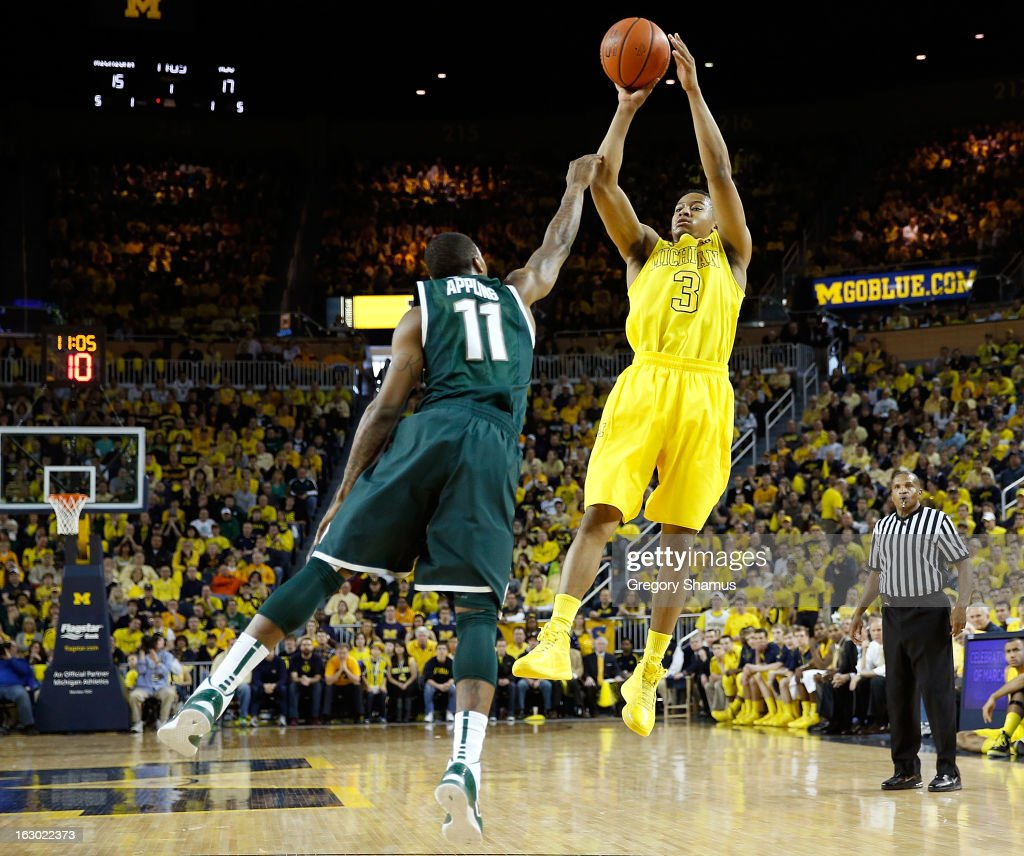 Trey Burke #3 of the Michigan Wolverines takes a first half shot over Keith Appling #11 of the Michigan State Spartans at Crisler Center on March 3, 2013 in Ann Arbor, Michigan.