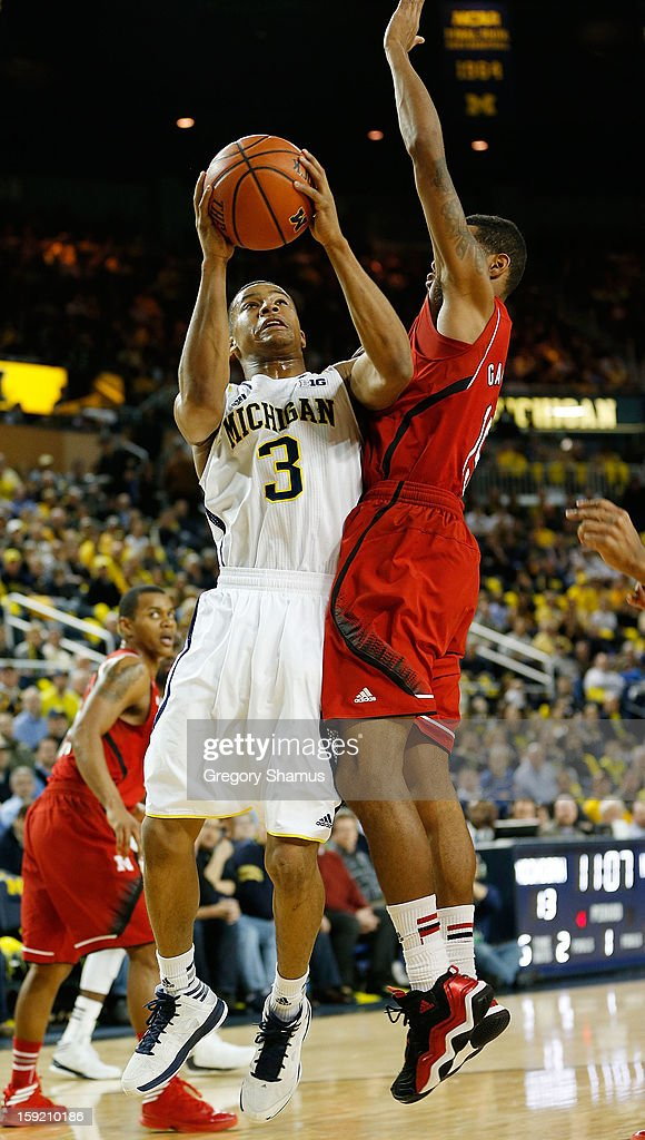 Trey Burke #3 of the Michigan Wolverines tries to get a first half shot off next to Ray Gallegos #15 of the Nebraska Cornhuskers at Crisler Center on January 9, 2013 in Ann Arbor, Michigan.