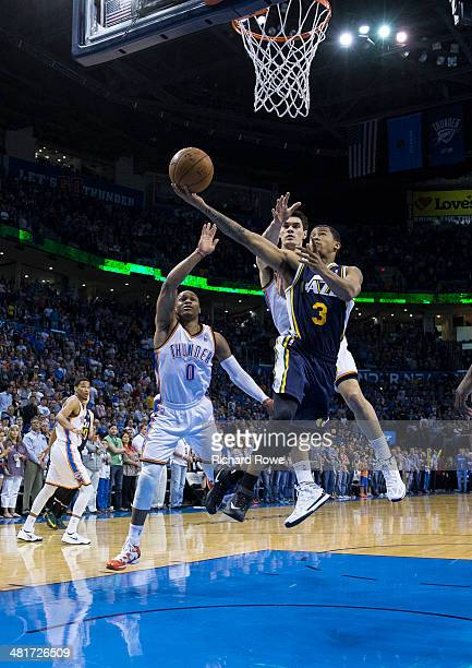 Trey Burke of the Utah Jazz drives to the basket against the Oklahoma City Thunder at the Chesapeake Arena on March 30 2014 in Oklahoma City Oklahoma...