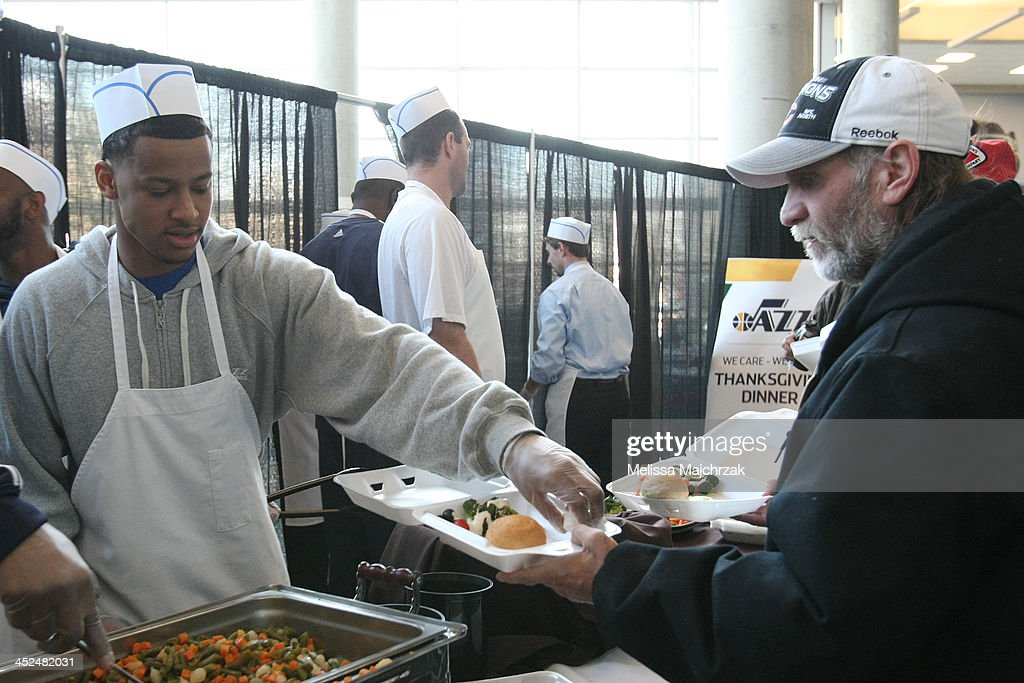 Trey Burke #3 of the Utah Jazz hands out food during the we care-we share Thanksgiving Dinner feeding the homeless at EnergySolutions Arena on November 27, 2013 in Salt Lake City, Utah.