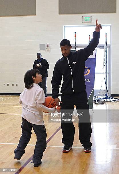 Trey Burke of the Utah Jazz points to the basket while a young fan shoots the basketball during a clinic showing students how to get fit at Glendale...