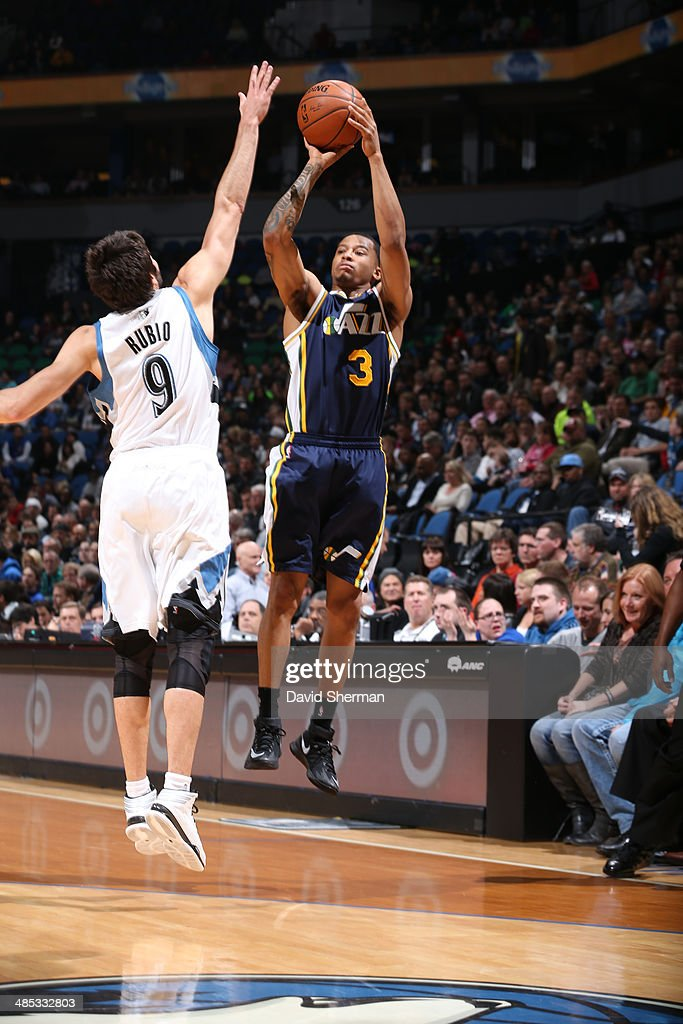 Trey Burke #3 of the Utah Jazz shoots against Ricky Rubio #9 of the Minnesota Timberwolves during the game on April 16, 2014 at Target Center in Minneapolis, Minnesota.