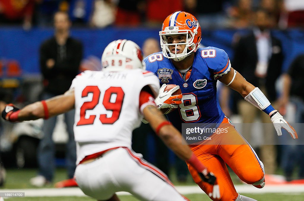 Trey Burton #8 of the Florida Gators carries the ball against Hakeem Smith #29 of the Louisville Cardinals during the Allstate Sugar Bowl at Mercedes-Benz Superdome on January 2, 2013 in New Orleans, Louisiana.