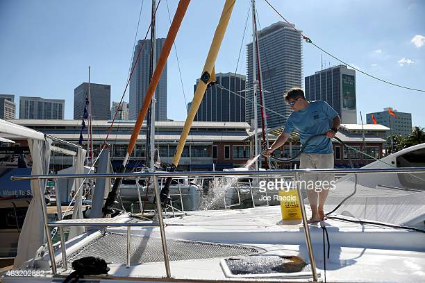 Trey Jaskiewicz cleans the deck of the Xquisite yacht as he prepares the boat for the opening of the The 2015 Miami International Boat Show on...