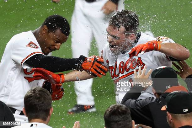 Trey Mancini of the Baltimore Orioles celebrates with Adam Jones at home plate after hitting a walk off three run homer to defeat the Pittsburgh...