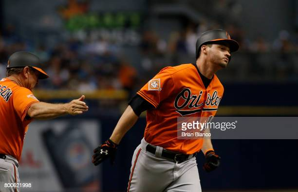 Trey Mancini of the Baltimore Orioles celebrates with third base coach Bobby Dickerson hitting a tworun home run off of pitcher Jumbo Diaz of the...