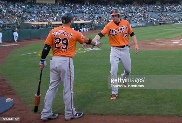 Trey Mancini of the Baltimore Orioles is congratulated by Welington Castillo after Mancini scored against the Oakland Athletics in the top of the...
