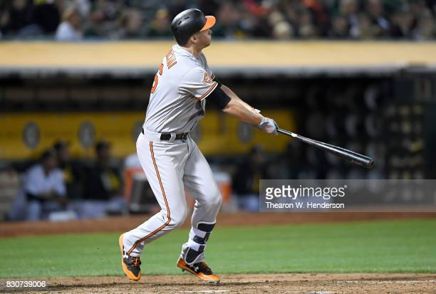 Trey Mancini of the Baltimore Orioles swings and watches the flight of his ball as he hits his second solo home run of the game against the Oakland...