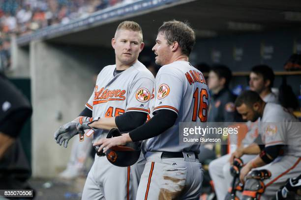 Trey Mancini of the Baltimore Orioles talks with Mark Trumbo of the Baltimore Orioles during a game against the Detroit Tigers at Comerica Park on...