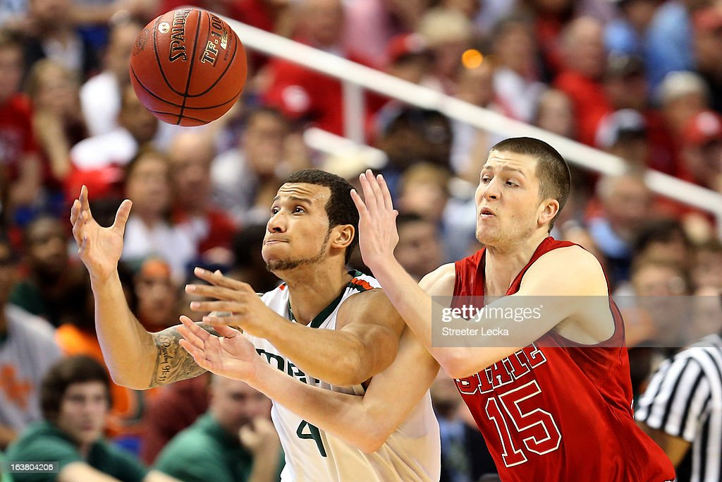 Trey McKinney Jones #4 of the Miami Hurricanes and Scott Wood #15 of the North Carolina State Wolfpack go after a loose ball during the men's ACC Tournament semifinals at Greensboro Coliseum on March 16, 2013 in Greensboro, North Carolina.