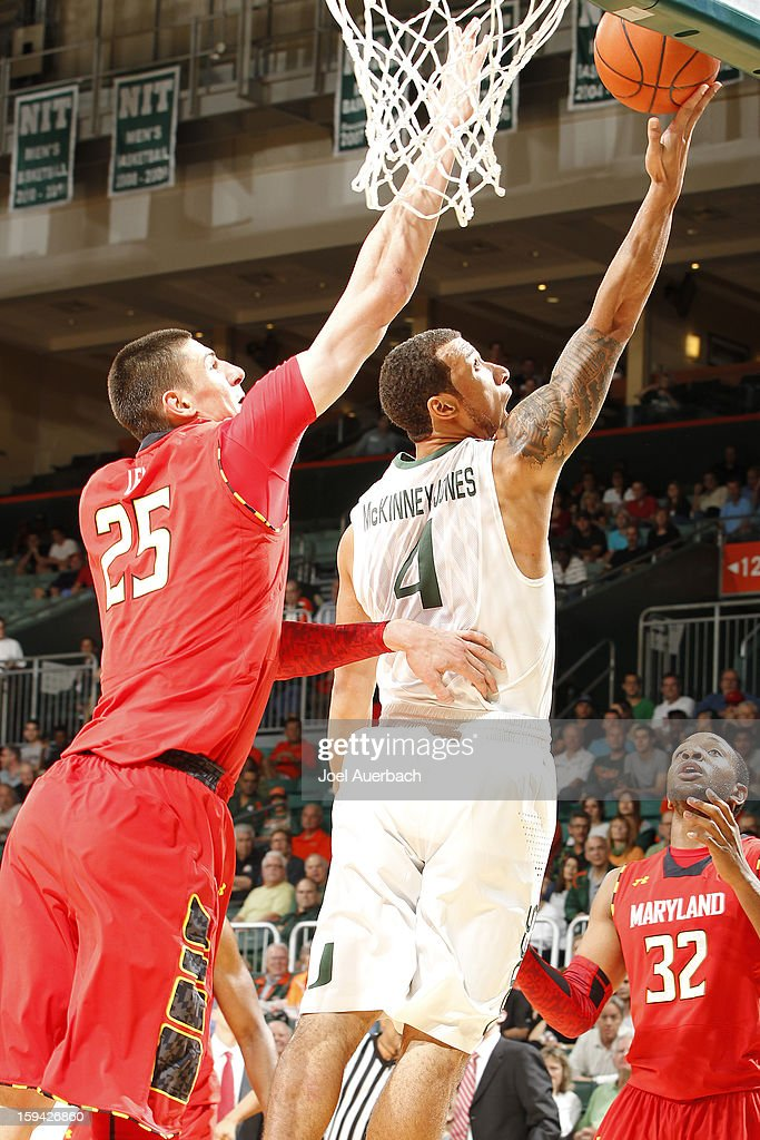 Trey McKinney Jones #4 of the Miami Hurricanes scores past Alex Len #25 of the Maryland Terrapins on January 13, 2013 at the BankUnited Center in Coral Gables, Florida.
