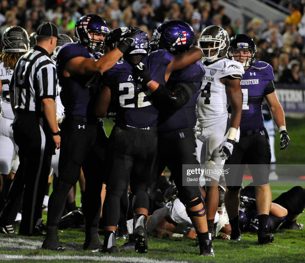 Treyvon Green #22 of the Northwestern Wildcats is greeted by his teammates after a touchdown against the Western Michigan Broncos during the third quarter on September 14, 2013 at Ryan Field in Evanston, Illinois.