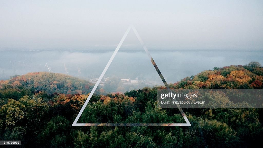 Triangle Shape Over Forest Against Cloudy Sky