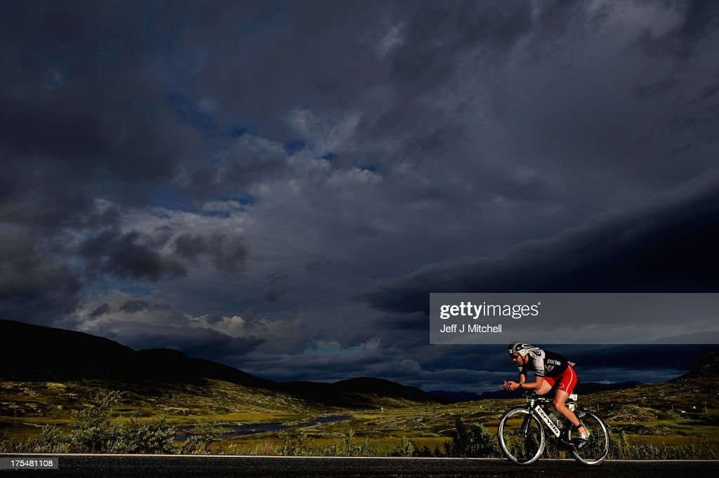 A triathlete cycles across the Hardangervidda mountain plateau during the Norseman Xtreme Triathlon on August 3, 2013 in Eodfjord, Norway.The race which was first held in 2003 runs point to point and is considered among many as the ultimate triathlon in the world. Owners and organisers Hardangervidda Triathlon Club limit the number of competitors to 250 they make their way through some of Norways most beautiful scenery during the course of the race.