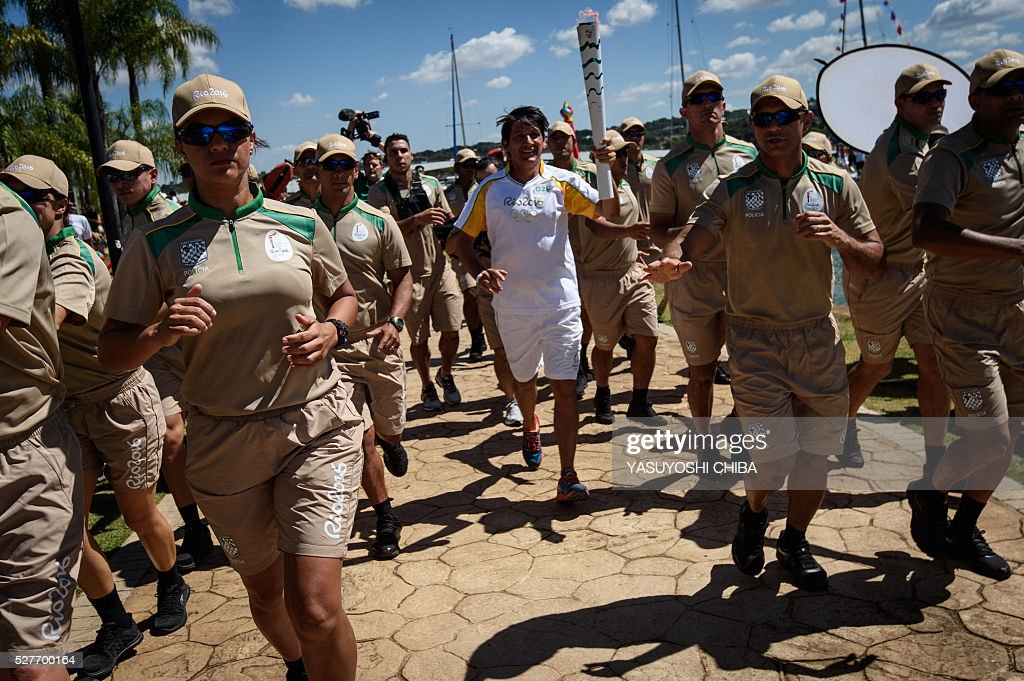 Triathlete Leandro Macedo carries the Olympic flame along Lake Paranoa in Brasilia on May 3. Embattled President Dilma Rousseff greeted the Olympic flame in Brazil on Tuesday, promising not to allow a raging political crisis, which could see her suspended within days, to spoil the Rio Games. The torch will now be carried in a relay by 12,000 people through 329 cities, ending in Rio's Maracana stadium on August 5 for the opening ceremony. / AFP / YASUYOSHI