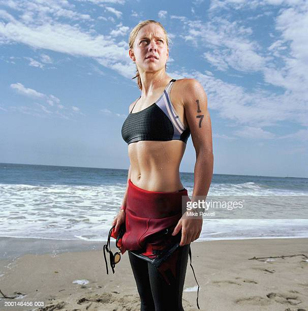 Triathlete on beach, wearing wetsuit, preparing for cycling