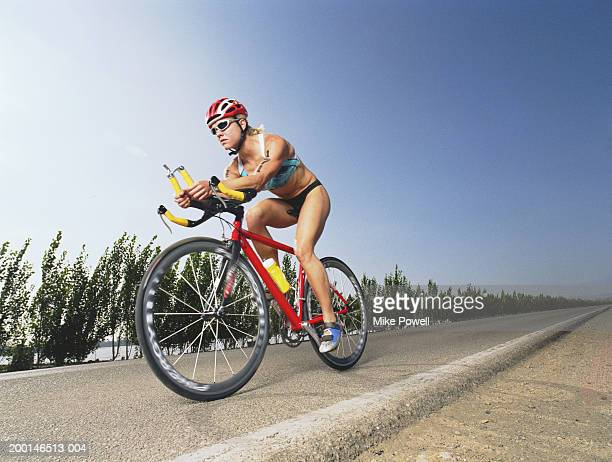 Triathlete riding bicycle down road in triathlon