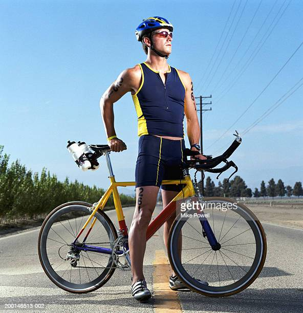 Triathlete standing in middle of road with bicycle