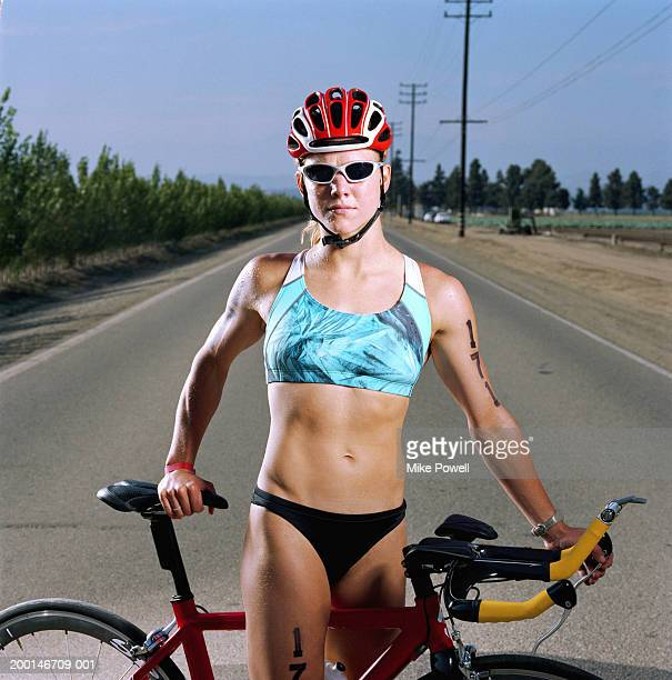 Triathlete standing in middle of road with bicycle, portrait