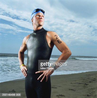 Triathlete standing on beach, wearing wetsuit