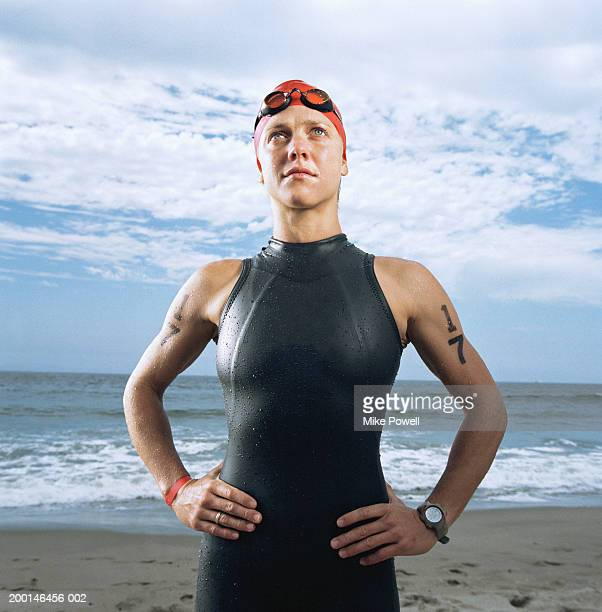 Triathlete wearing wetsuit, standing on beach, looking outward