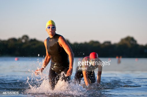 Triathlon Participants Running in The Water.