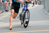 runner is running near his bicycle at triathlon