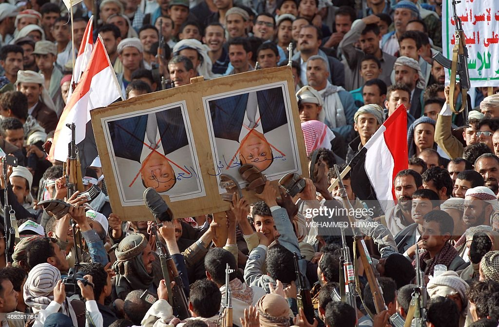 Tribal gunmen loyal to the Huthi movement deface a portrait of Yemeni President Abedrabbo Mansour Hadi with shoes in the capital Sanaa on April 1, 2015, during a demonstration against Saudi-led coalitions Operation Decisive Storm against the Huthi rebels in Yemen.