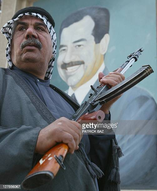 A tribesman holds his kalashnikov assaultrifle during a show of strength by members of Jaish alQuds militia in Baghdad's Saddam City 10 March 2003...