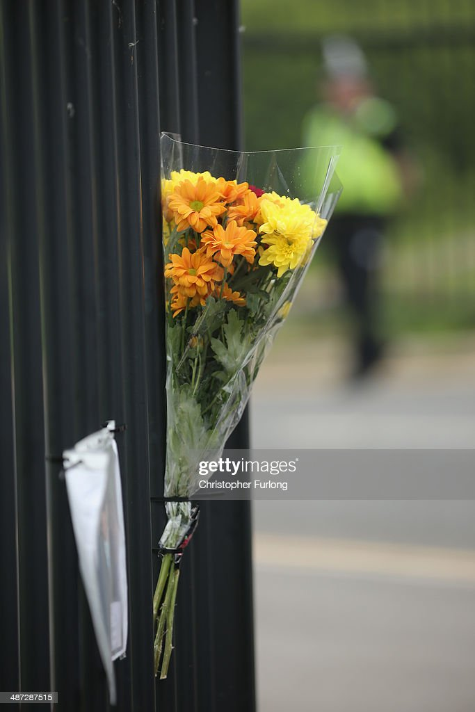 Tributes adorn the school fence as schoolchildren arrive at Corpus Christi Catholic College in Neville Road on April 29, 2014 in Leeds, England. A fifteen year old male student has been arrested in connection with the death of teacher Anne Maguire who was fatally stabbed yesterday during lessons at Corpus Christi Catholic Catholic College.