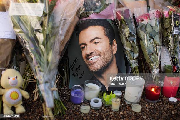 Tributes of flowers photographs and candles are left outside the home of pop music icon George Michael in The Grove Highgate on December 28 2016 in...