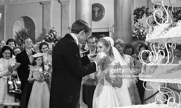 Tricia Nixon and Ed Cox enjoying their wedding cake at the White House