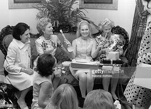 Tricia Nixon holds up a gift she received during her bridal shower May 26 1971 at the White House Also pictured is Helen Thomas and Patricia Nixon