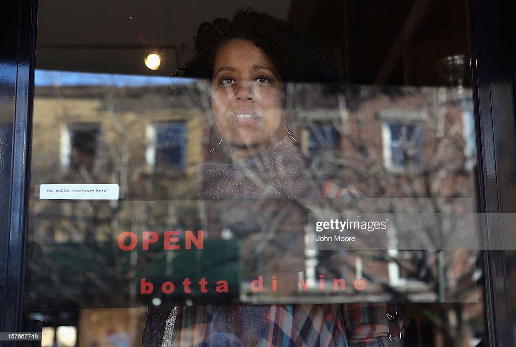 Triciann Botta, owner Botta di Vino, looks from the front door of her wine store in the Red Hook neighborhood of Brooklyn on December 5, 2012 in New York City. Although she was able to reopen her store, many businesses in the area remain closed more than a month after superstorm Sandy flooded the area. With many residents still unable to move back into their homes, Botta said business remains very low in the area.
