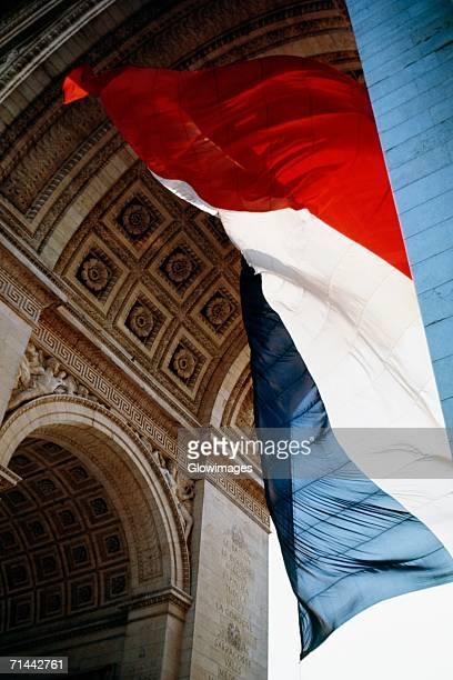 Tri-color flag fluttering under Arc De Triomphe, Paris, France