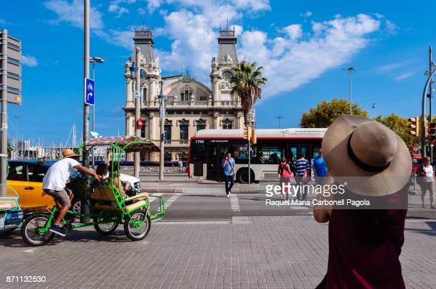 Tricycle carrying a couple of tourists in Passeing de Colom in front of Historic Port Authority building